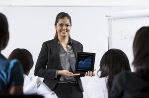 Indian Business woman discussing finance chart on a touch pad.